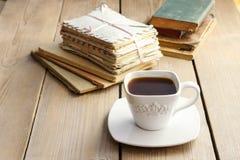 Taza de café en la tabla de madera Libros del vintage y pila de letras Fotos de archivo