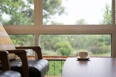taza de café en la tabla de madera, silla de cuero cerca de la ventana con el jardín Imagen de archivo