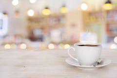 Taza de café en la tabla de madera sobre fondo defocused de la cafetería imagen de archivo libre de regalías