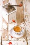 Taza de café en la tabla de madera vieja con el molino de café retro Imágenes de archivo libres de regalías