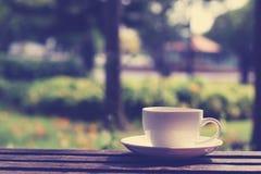 Taza de café en la tabla en el jardín Foto de archivo libre de regalías