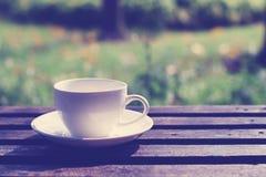 Taza de café en la tabla en el jardín Fotos de archivo libres de regalías