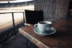 Taza de café en la tabla en estadio Imagenes de archivo