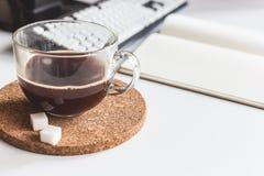 Taza de café en la tabla en oficina Imágenes de archivo libres de regalías