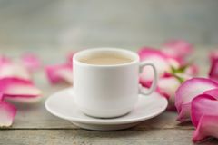 Taza de café en la tabla de madera rústica en un marco de rosas rosadas g Imágenes de archivo libres de regalías