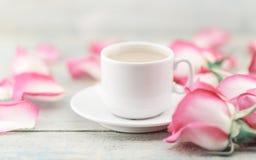 Taza de café en la tabla de madera rústica en un marco de rosas rosadas g Fotografía de archivo libre de regalías