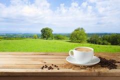 Taza de café en la tabla de madera sobre fondo hermoso del paisaje foto de archivo libre de regalías