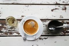 Taza de café en la tabla de madera vieja con la pequeña taza de taza del té y del azúcar imagen de archivo