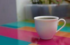 Taza de café en la tabla superior colorida en fondo de la falta de definición imagenes de archivo