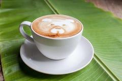 Taza de café en licencia de la palma Foto de archivo libre de regalías