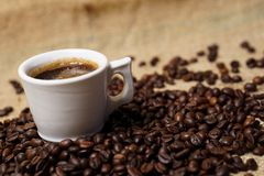 Taza de café en los granos de café foto de archivo
