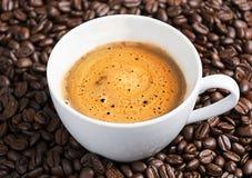 Taza de café en los granos de café asados como fondo imagen de archivo