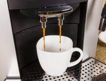 Taza de café en máquina Foto de archivo