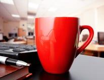 Taza de café en oficina Fotos de archivo libres de regalías