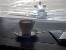 Taza de café en salón del negocio del ` s del aeropuerto con los aviones