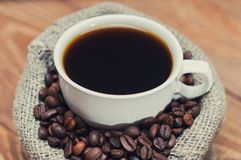 Taza de café en un bolso de granos Fotos de archivo libres de regalías