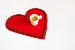 Taza de café en un corazón rojo del fieltro Imagenes de archivo