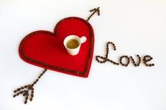 Taza de café en un corazón rojo del fieltro con la flecha y el amor Fotos de archivo libres de regalías