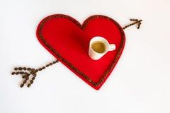 Taza de café en un corazón rojo del fieltro y de flecha en diagonal Foto de archivo libre de regalías