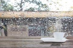Taza de café en un día lluvioso con luz del sol de la mañana Imagen de archivo