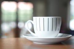 Taza de café en un escritorio de madera Foto de archivo libre de regalías