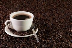 Taza de café en un fondo de los granos de café Imagen de archivo libre de regalías
