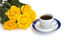 Taza de café en un platillo blanco y un ramo de rosas amarillas Foto de archivo libre de regalías