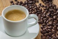 Taza de café en un platillo y granos del café sólo Imagen de archivo libre de regalías