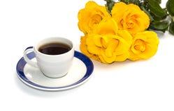 Taza de café en un platillo y un ramo de rosas amarillas, la imagen aislada Imagen de archivo libre de regalías