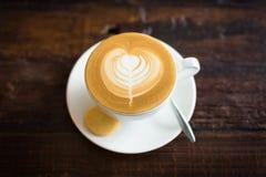 Taza de café en un vector de madera Latte en forma de corazón de la espuma del café imagen de archivo