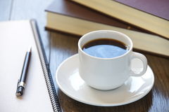 Taza de café en una pila de libros fotografía de archivo