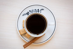 Taza de café en una placa con el azúcar marrón y el palillo de canela imagen de archivo