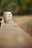 Taza de café en una repisa o una pared foto de archivo