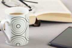 Taza de café en una tabla con un teléfono elegante Imagenes de archivo