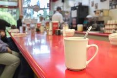 Taza de café en una tabla de la barra Imagen de archivo libre de regalías