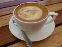 Taza de café en una tabla de madera Fotografía de archivo libre de regalías