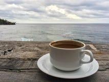 Taza de café en una tabla de madera con una vista al mar foto de archivo