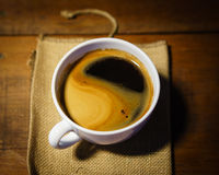 Taza de café en una tabla de madera Fondo oscuro imagenes de archivo