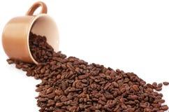 Taza de café enmascarada y granos de café asados Foto de archivo libre de regalías