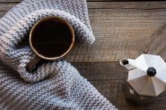Taza de café envuelta en bufanda caliente en el tablero de madera Visión superior, estilo del vintage, aún vida Fotos de archivo