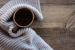 Taza de café envuelta en bufanda caliente en el tablero de madera Visión superior, estilo del vintage, aún vida Endecha plana Foto de archivo libre de regalías