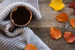 Taza de café envuelta en bufanda caliente en el tablero de madera Visión superior, estilo del vintage, aún vida Endecha plana Imagen de archivo
