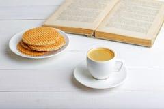 Taza de café express, de galletas y de libro Fotos de archivo libres de regalías