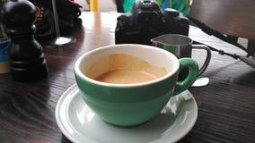 Taza de café express del café y de una cámara Foto de archivo libre de regalías