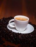 Taza de café express y de habas en una tabla de madera Imagenes de archivo