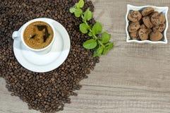 Taza de café fresco, de granos de café, de galletas con el chocolate y de flores de la menta Fotografía de archivo
