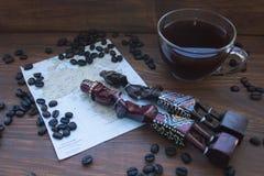 Taza de café, granos de café, mapa de África y estatuas de madera imágenes de archivo libres de regalías