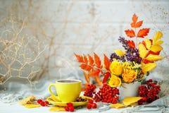 Taza de café, de hojas de otoño y de flores en una tabla de madera Todavía del otoño vida Foco selectivo Foto de archivo libre de regalías