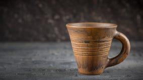 Taza de café de la arcilla del vintage en el escritorio rústico de madera oscuro foto de archivo