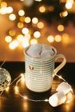 Taza de café de la Navidad con las melcochas en el fondo de las luces y de las decoraciones del ` s del Año Nuevo Foto de archivo libre de regalías